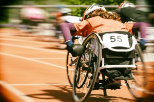 Athletes  at a wheelchair race in a stadium with motion blur, lens vignetting and  Nik collection Analog Efex Pro 2 film effect